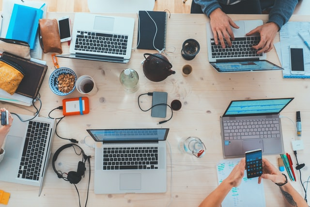 A bunch of laptops on a wooden table with coffee mugs, laptops, headphones as well as a teapot, mugs of tea and a bowl of emptied pistachio shells
